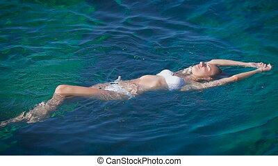 A young happy woman in the white bikini swimming in azure sea