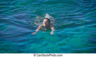 A young happy woman swimming in azure sea. Closeup, slow...