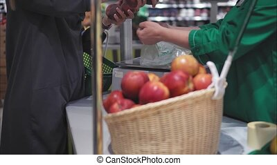 A young hipster female weigh fruits in the store