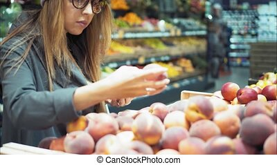 A young hipster woman chooses peaches in the store