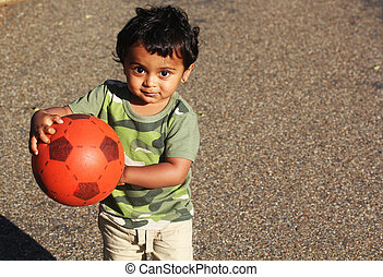 A Young Indian Toddler playing with a red ball in a green ...