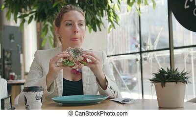 A Young Lady Eating Sandwich in the Cafe - A young lady...