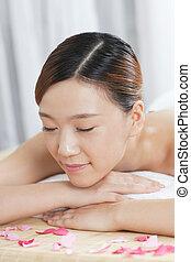 A young lady enjoying stone massage at spa