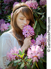 A young lady enjoys the smell of a rhododendron blossom - A...