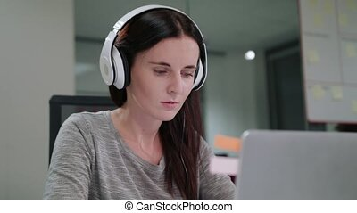 A Young Lady Listening to Music on the Laptop