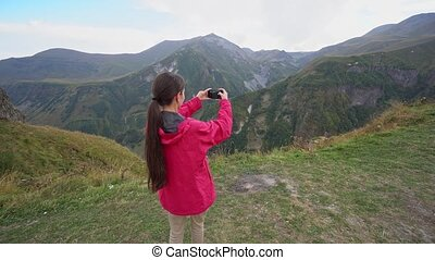 A Young Lady Taking Photos in the Mountains. - A young lady...