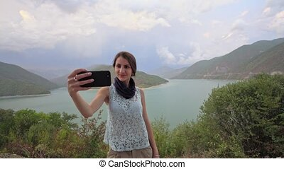A Young Lady Taking Selfie Near the Lake. - A young lady...