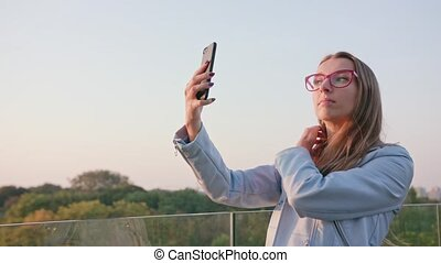 A Young Lady Taking Selfie Outdoors - A young beautiful lady...