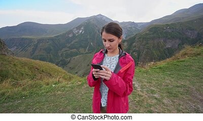 A Young Lady Using a Smartphone in the Mountains.