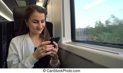 A Young Lady Using a Smartphone in the Train.