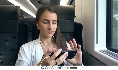 A Young Lady Using a Smartphone in the Train. - A young lady...