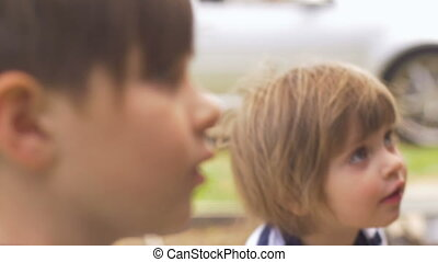 A young little boy and girl asking questions and playing outside