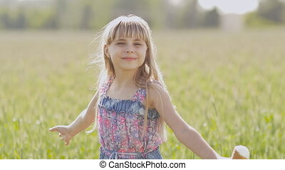 A young little girl beautifully turns on a warm sunny afternoon with ice cream in the hands against the background of a wheat field.