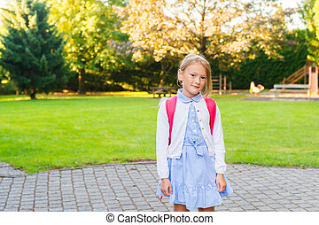 A young little girl preparing to walk to school