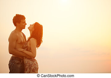 A young  loving  couple hugging and kissing on the beach at sunset. Two lovers, man and woman near the water. Summer in love