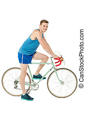 A young male bicyclist riding a bicycle