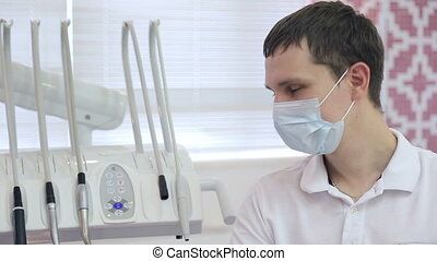 A young male dentist, disposable mask, next to dental...