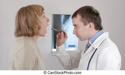 A young male doctor examines the throat of an aged woman. The man says the diagnosis and prescribes treatment.