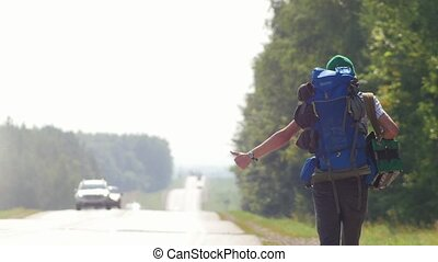 A young male hitchhiker with a large backpack zoom and goes...