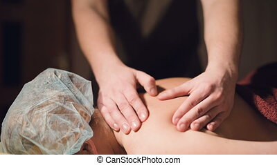 A young male masseur does a professional massage client girl in a professional massage parlor with lit candles in a dark room.