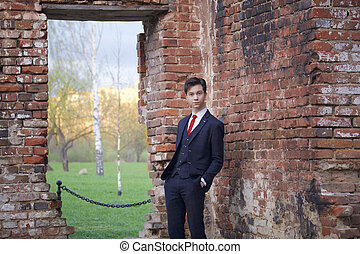 A young man, a teenager, in a classic suit. Foolishly stands opposite the old wall of red brick, putting his hands in his pockets.