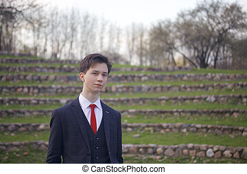A young man, a teenager, in a classic suit. It stands on the stone steps of the summer amphitheater, putting his hands in his pockets.
