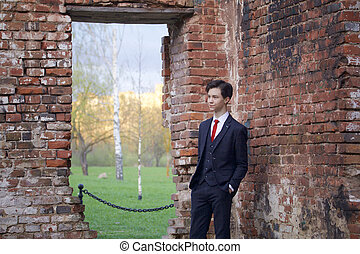 A young man, a teenager, in a classic suit. Pondering is standing in front of the old wall of red brick, putting his hands in his pockets.
