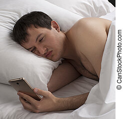 a young man after sleeping, in his hand holds the phone.