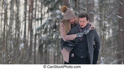 A young man and a woman in a coat are having fun and playing with snow in a winter forest in slow motion. Happiness and smiles on faces