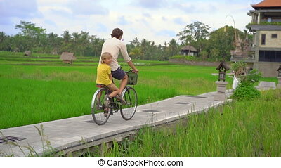 A young man and his little son ride through the beautiful rice field on a bicycle. Travel to South-East Asia concept. Slow motion shot