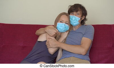 A young man and woman during self-isolation sit at home on a couch. The man hugs his scared wife. They wear medical face masks