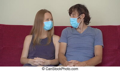 A young man and woman during self-isolation sit at home on a couch. They look at each other. They wear medical face masks