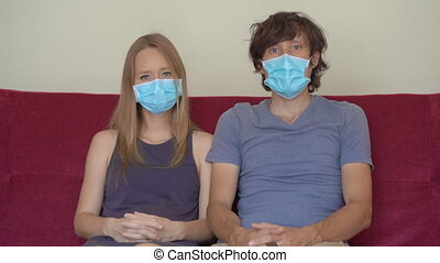 A young man and woman during self-isolation sit at home on a couch. They look at the camera. They wear medical face masks