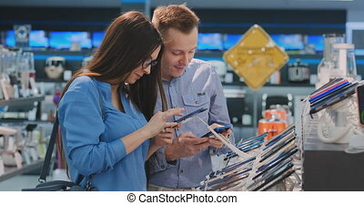 A young man and woman hold in their hands two smartphones standing around a showcase with smartphones in an electronics store choosing from two the best. Comparison of two devices. Large selection of products