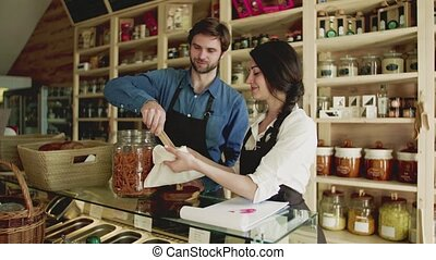 A young man and woman shop assistant working in a zero-waste store or shop.
