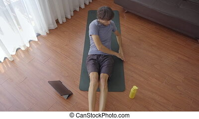 A young man at home doing physical exercises following instructions from a video he watches on a tablet. Social distancing concept. Internet trainer concept.