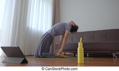 A young man at home doing yoga following instructions from a video he watches on a tablet. Social distancing concept. Internet trainer concept.