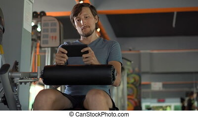 A young man at the gym doing exercises holding a phone in front of his eyes in his hands. All the attention is in the phone. The concept of dependence on social networks. Mobile addiction concept