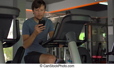 A young man at the gym on an exercise bike holding the phone...
