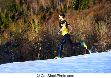 A young man athlete runs in the snow
