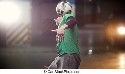 A young man balancing the ball on his head and back. Mid...