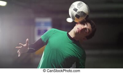 A young man balancing the ball on his head and shoulders....