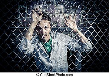 a young man behind bars close