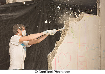 A young man breaks a partition in the apartment with a hammer