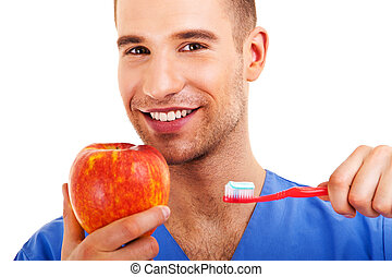 A young man brushing his teeth and holding apple isolated on...