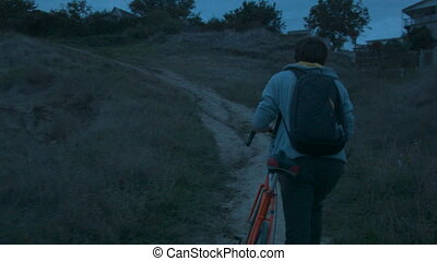 A young man climbs up a mountain with a bike at dusk