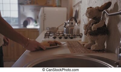 A Young Man Comes to the Kitchen in the Morning. He Picks up a Plate of Cookies from the Table.