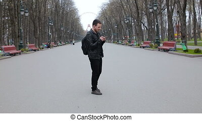 A young man dances in the park and listens to music on the smartphone