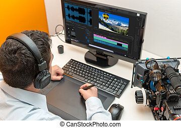 young man designer using graphics tablet for video editing -...