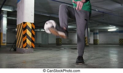 A young man doing football tricks on the underground...